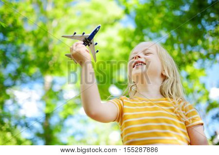 Adorable Little Girl Playing With Small Toy Airplane Outdoors
