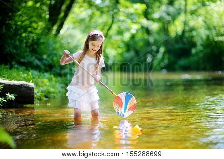 Cute Little Girl Playing In A River Catching Rubber Ducks With Her Scoop-net