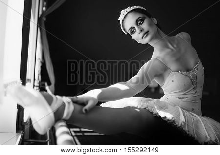 Beautiful young ballerina ballet dancer warming up and stretching trains in the dance studio