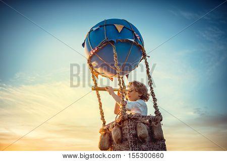 Boy with a spyglass on a balloon