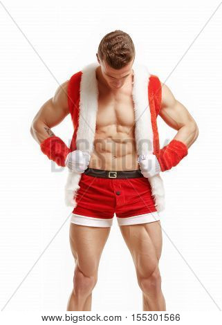 Muscular fitness man in a suit of Santa Claus. Fitness Santa Claus with perfect muscular body showing six pack abs. Strong Athletic Man Fitness Model Torso showing six pack abs.