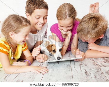 Children and dog with tablet. Group kids playing
