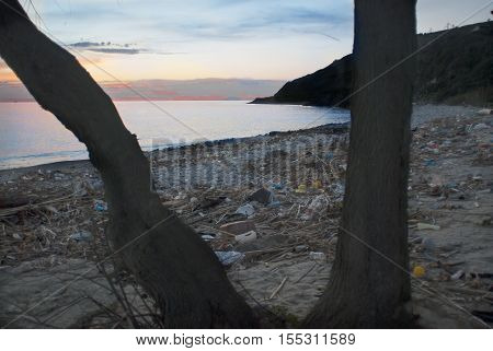 sunset at sea on a polluted beach
