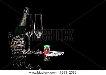 Bottle of champagne in an ice bucket with two wineglasses and cards and colorful poker chips
