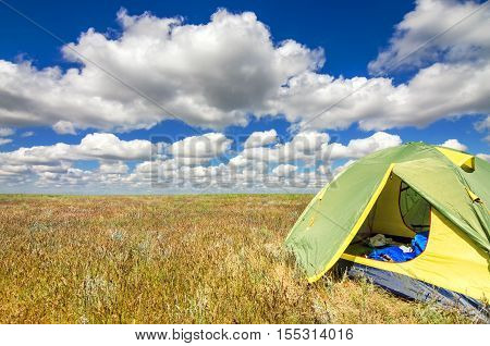 A touristic green tent set up in astrakhan steppe under beautiful sky shoot in May. Spring is beautiful time. Steppe are green and covered by emerald grass. Panorama of steppe near salt lake Baskunchak, Russia
