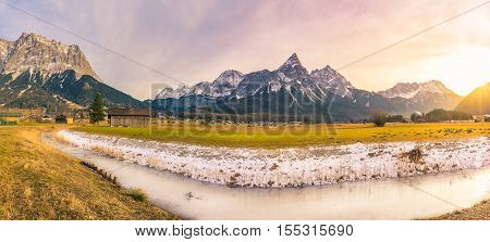 Alpine winter panorama in the afternoon - Beginning of the winter in the Austrian Alps mountains with a frozen river snow on the dried grass a small village and a bright afternoon sun.