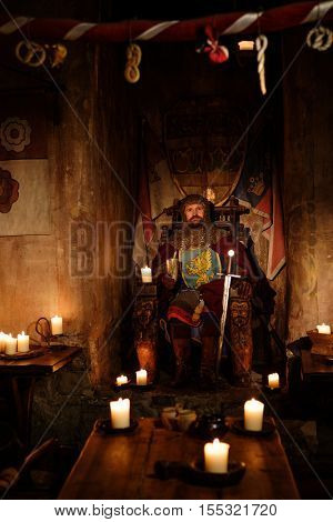 Old medieval king on the throne in ancient castle interior.