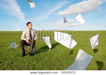 A businessman in a field sat with his paperwork flying around him.