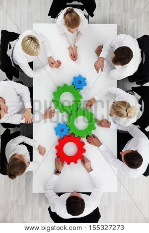 Business team sitting around the table with cogs teamwork concept