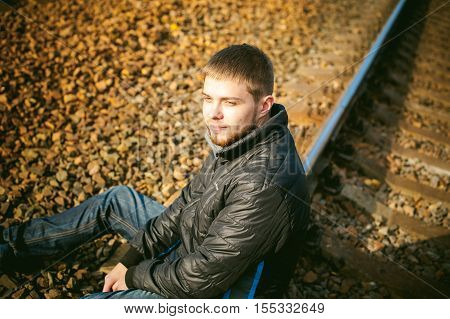 A Young Man Sitting On The Tracks. Bearded Guy In A Jacket And Jeans, Sitting On The Rails And The S