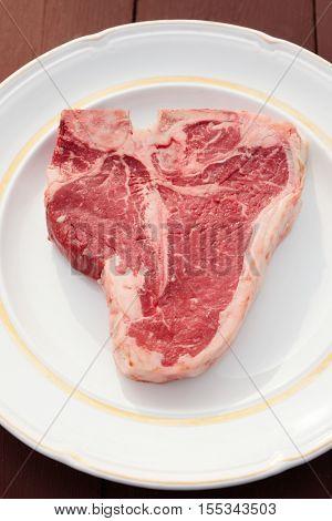T-bone steak in a white rustic plate
