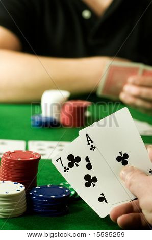 People playing Texas hold 'em Poker around a gambling table.