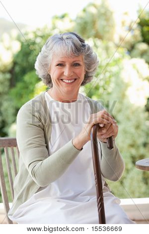 Retired woman with her walking stick at home