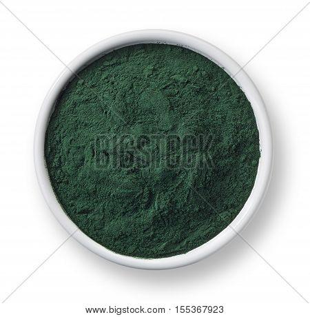White bowl of spirulina algae powder isolated on white background