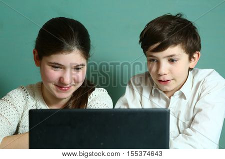 teen siblings brother and sister at the laptop playing computer games smiling