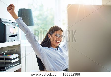 Joyous female entrepreneur in small office with extended arms as if to celebrate something wonderful such as a business deal