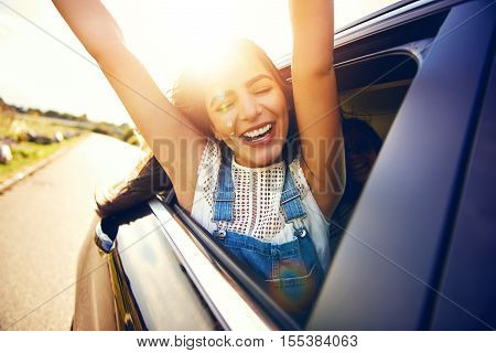 Woman leans out car window and waves her arms as it zooms through the countryside