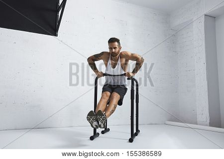 Strong tattooed in white unlabeled tank t-shirt male athlete shows calisthenic moves Straight dips move two, dip in on one of parallel bars