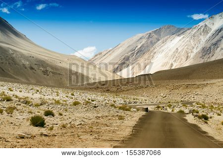 A concrete road towards beautiful rocky mountains and blue sky with peaks of Himalaya Leh Ladakh Jammu and Kashmir India