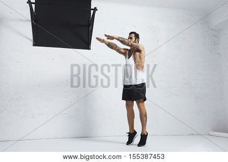 Strong tattooed in white unlabeled tank t-shirt male athlete shows calisthenic moves Squat calf rises, top position