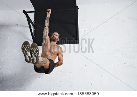 Strong tattooed in white unlabeled tank t-shirt male athlete shows calisthenic moves Hanging on pull bar one arm leg raises or l-sit hold