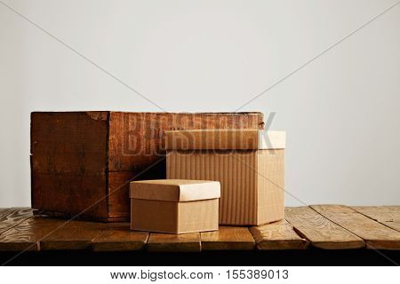 Unlabeled brown cardboard boxes with covers arranged next to a worn brown wooden crate against white wall background