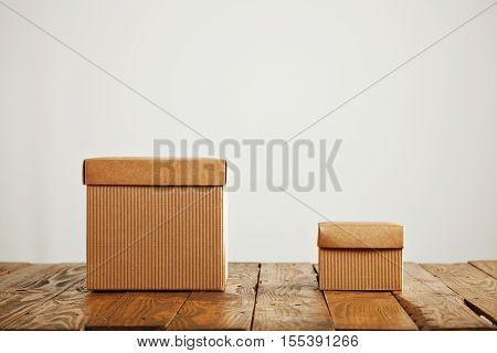 Two unlabeled craft cardboad boxes of different sizes presented in a studio with white walls on a rough wooden table