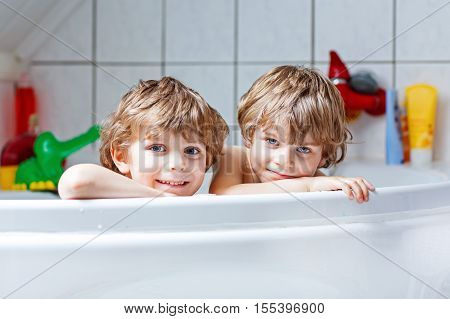 Happy siblings: Two little twins children playing together with water by taking bath in bathtub at home. Kid boys having fun together, helping with hair washing.