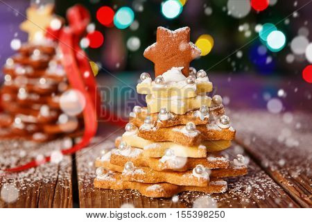 Home made baked Christmas gingerbread tree as a gift for family and friends on wooden background. With colorful lights from Christmas tree on background. With icing sugar gift for xmas.