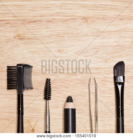 Accessories for care of the brows: brow comb / brush combo, spoolie brush, eyebrow pencil, tweezers, angled brush on wood background. Eyebrow grooming tools. Copy space