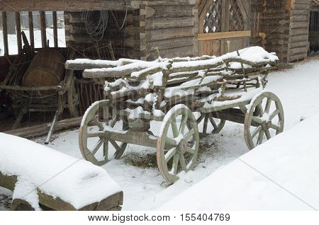 Wooden wagon is in the yard covered with snow.
