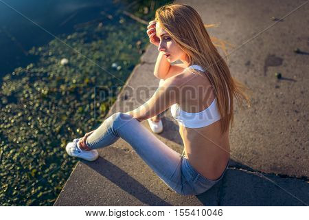 young athletic girl in a short white top and gray jeans and white shoes sitting near the pond and sad