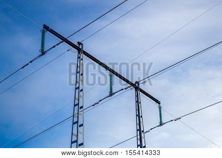 High voltage power transmission towers with blue sky in the background