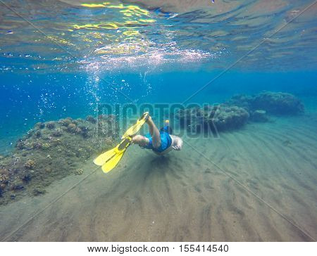 Underwater landscape with snorkel and coral reef. Snorkeling man in mask swimming undersea. Swimmer in yellow fins. Diving in tropical seaside. Blue lagoon with corals and coral fishes