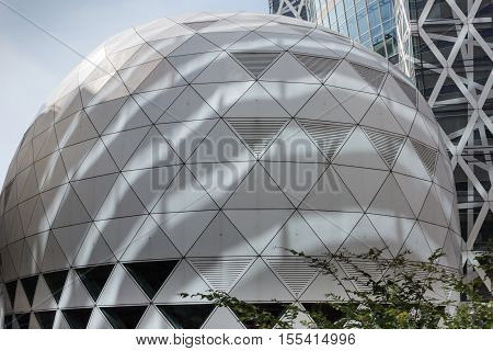 Tokyo Japan - October 2 2016: Closeup of the dome adjacent to the Cocoon Tokyo Mode Gakuen building in Shinjuku neighborhood. Blue sky. Metal and glass construction with lots of triangles.