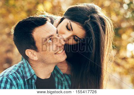 Surprise kiss girl kissing her boyfriend in the cheek