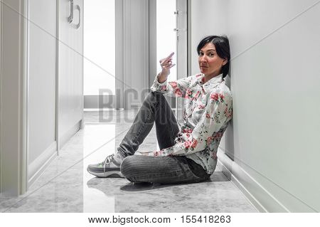 Young Woman Showing Middle Finger Gesture On The Floor
