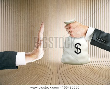 Hand saying no to money bag on wooden background. Stop corruption concept