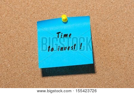 Time to Invest inscription written on blue sticker pinned to cork notice board.