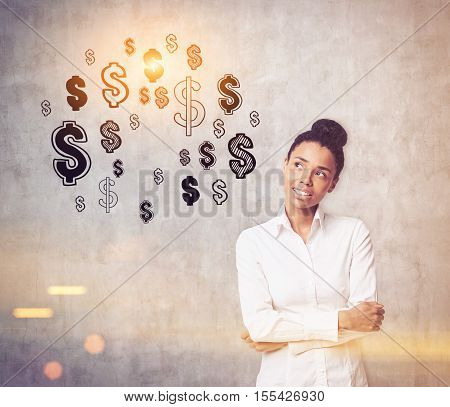 African American girl is standing against concrete wall with dollar signs on it and thinking. Concept of earning money. Toned image