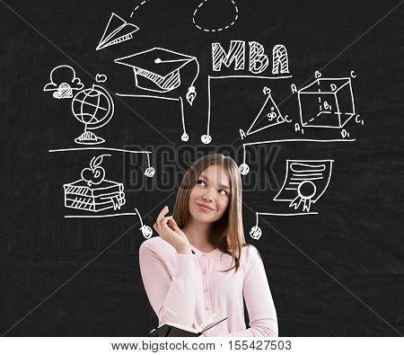 Young woman in pink sweater is standing near black wall with education sketches. Concept of knowledge getting