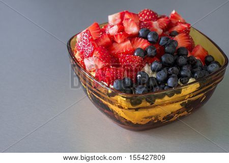 Fresh cottage cheese with cut strawberries and blueberry in yellow glass bowl. Healthy breakfast.