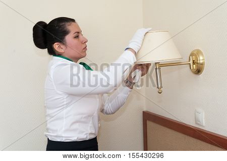 MOSCOW - OCTOBER 31: Supervisor girl dressed in white and black checking cleanliness of lamp at room in Izmaylovo hotel on October 31 2016 in Moscow. Izmailovo Hotel is four-building hotel located in Izmaylovo District of Moscow.