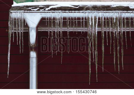 Winter season scene. Icicles on the roof. cold weather concept. Frozen icy down pipe waterspout