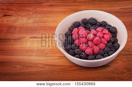 Ceramic plate with heart shaped berries on the right of the wooden table with clipping path. Top side view. Top side view.