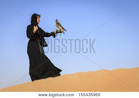 Woman in abaya with Peregrine Falcon in Dubai Desert Conservation Reserve, UAE