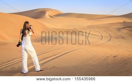 A woman is taking photos of dunes in Desert Conservation area near Dubai, UAE