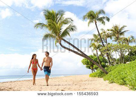 Hawaii beach couple walking on hawaiian beach, Kaanapali beach, Maui, Hawaii, USA. Travel vacation Asian, Caucasian couple relaxing on famous hawaiian beach destination for summer travel holidays.