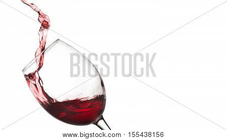 Red wine splashing. Pouring wine into crystal glass, close-up, white background.