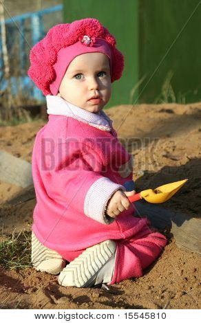 child in pink clothes play in sandbox yellow shovel